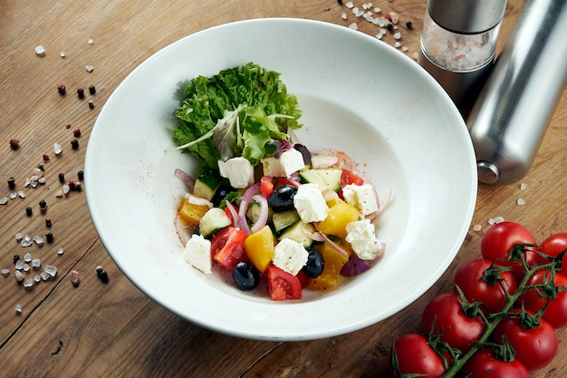 Classic greek salad with tomatoes, onions, cucumber, feta cheese and black olives in pita on a white plate on a wooden surface.