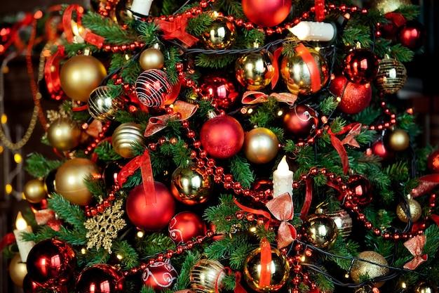 어두운 방에서 번쩍이는 갈 랜드와 함께 고전적인 녹색 크리스마스 트리. 크리스마스 인테리어