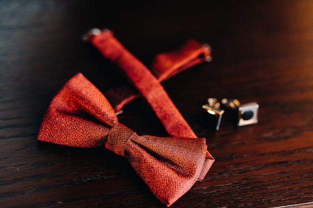 Classic groom accessories: red bow tie and cufflinks on the table. morning of the groom.