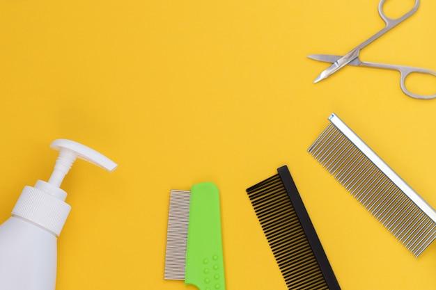 노란색 배경에 있는 고전적인 손질 및 미용 도구:로션, 비누, 빗, 가위. 평면도, 하단 배치, 레이아웃, 복사 공간