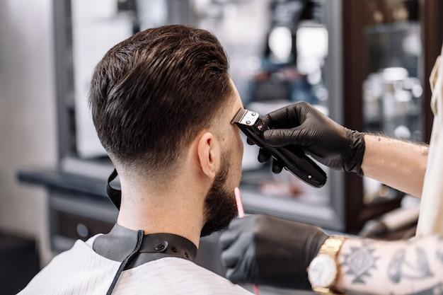 理髪店での古典的なヘアカット。理髪店でのカーブヘアスタイリングとヘアヘルスケア。男性用