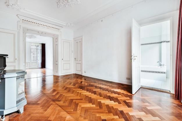 흰 벽과 장식용 치장 벽토 요소와 벽난로가있는 쪽모이 세공 마루가있는 넓은 복도의 고전적인 홈 인테리어 디자인