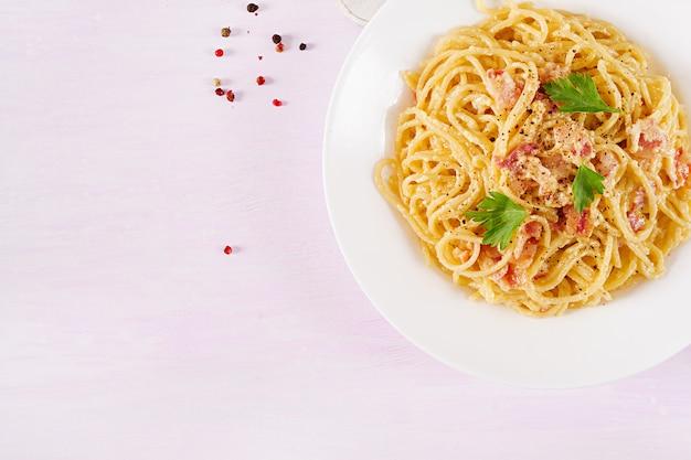 パンチェッタ、卵、ハードパルメザンチーズ、クリームソースが付いたクラシックな自家製カルボナーラパスタ。