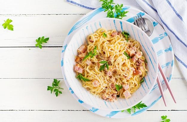 Classic homemade carbonara pasta with pancetta, egg, hard parmesan cheese and cream sauce. italian cuisine. spaghetti alla carbonara. top view, copy space