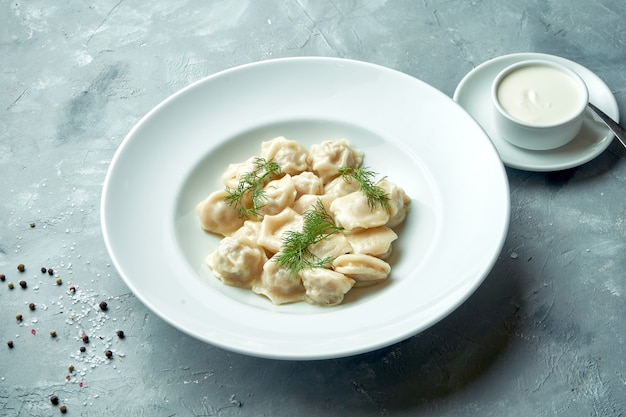 灰色の背景に白い皿にミンチ肉とサワークリームと古典的な自家製餃子