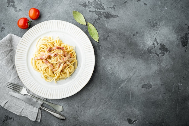 Классическая домашняя паста карбонара по-итальянски с беконом, яйцами, сыром пармезан, на сером каменном столе, плоская планировка, вид сверху, с копией пространства