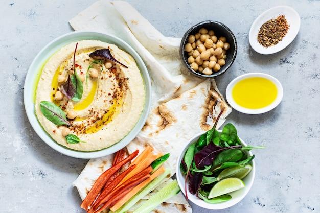 Классический хумус в миску с травами, копченой паприкой, оливковым маслом и салатом на синем (сером) фоне. здоровая веганская еда.