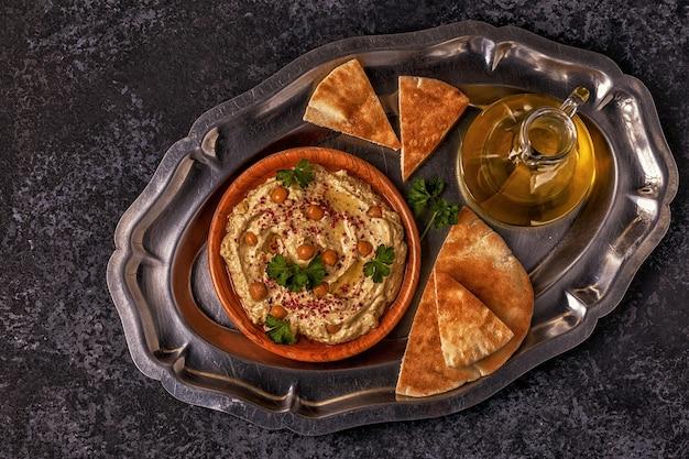Классический хумус с петрушкой на тарелке и лавашем