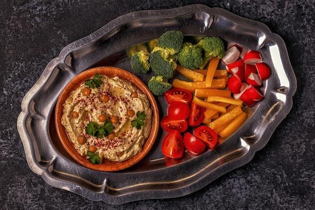 Классический хумус с овощами на тарелке