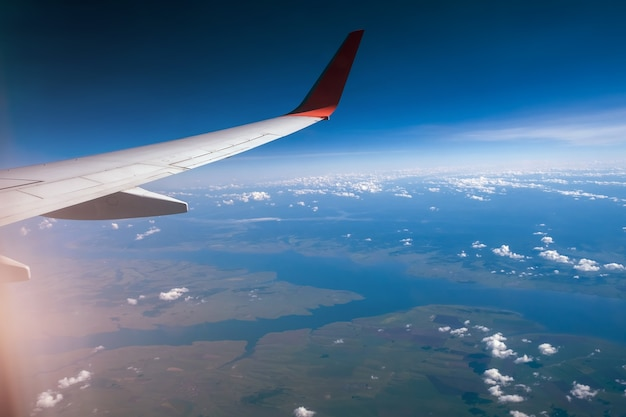 Classic image through aircraft window onto wing flight view over russia