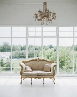 소파와 큰 창문이있는 거실의 고전적인 인테리어