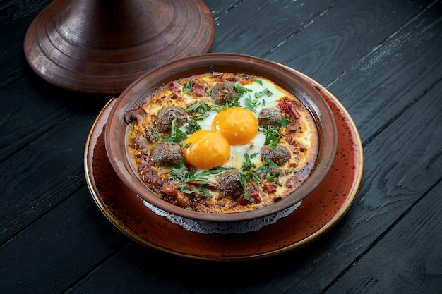 Classic israeli scrambled eggs - shakshuka with tomatoes, herbs and meat kebabs, served in a clay plate on a black surface