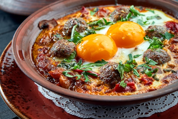 Classic israeli scrambled eggs - shakshuka with tomatoes, herbs and meat kebabs, served in a clay plate on a black surface.