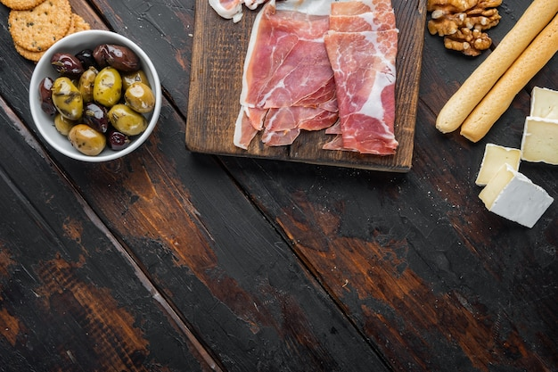 Classic italian antipasti set, on dark wooden table, flat lay