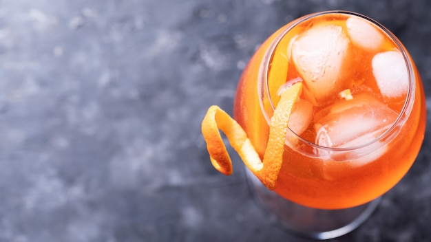 Classic italian aperitif aperol spritz cocktail in glass with slice of orange on dark wall, top view