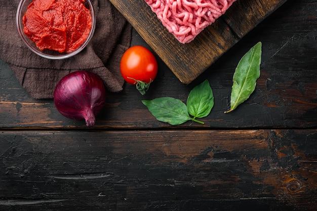 Классические итальянские ингредиенты соуса болоньезе, мясной фарш, помидоры и зелень, на деревянной разделочной доске, на старом темном деревянном столе, вид сверху, плоская планировка