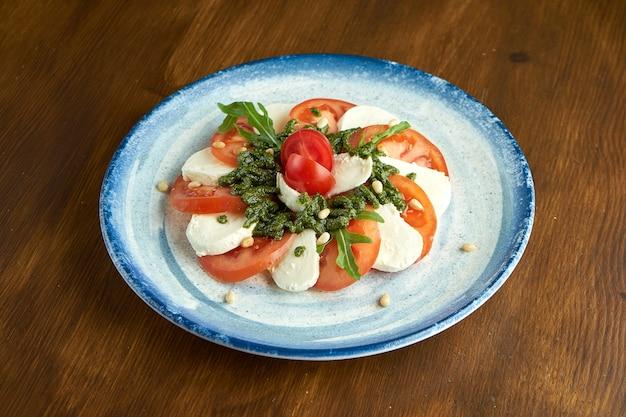 Классический итальянский салат капрезе с помидорами, моцареллой, рукколой и соусом песто в синей тарелке на деревянной поверхности