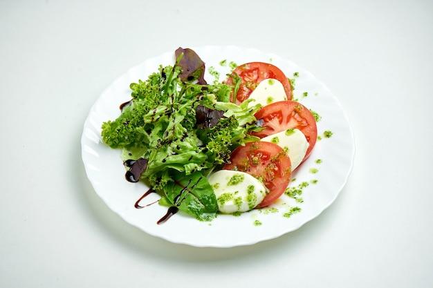 Классический итальянский салат капрезе с помидорами, моцареллой, микс салатом и соусом песто в белой тарелке на белой тарелке
