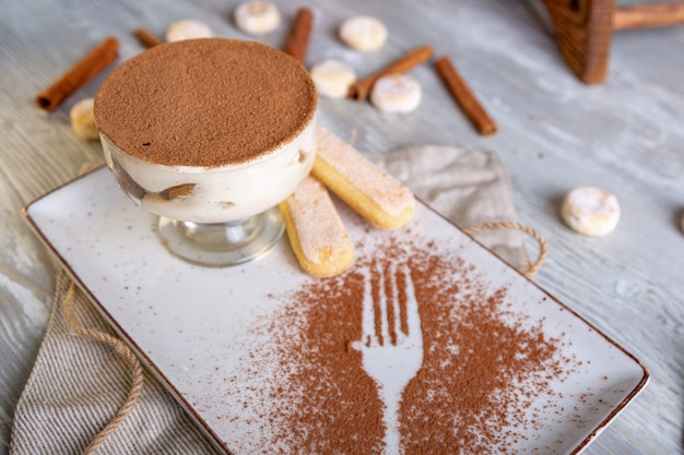 A classic italian dessert tiramisu in a bowl with an atmospheric serving of tea.