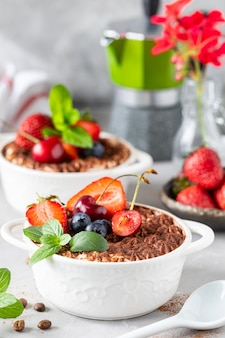 Classic italian dessert tiramisu decorated with strawberries, cherries and mint on a white background.