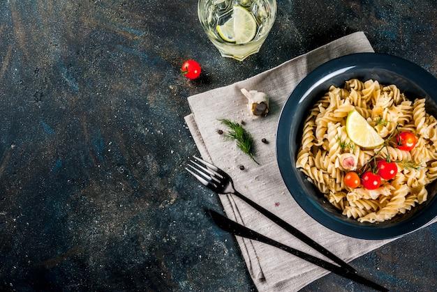 ペストソーストマトライムと暗いボウル暗い青色の背景で新鮮なハーブの古典的なイタリアのパスタフジッリ