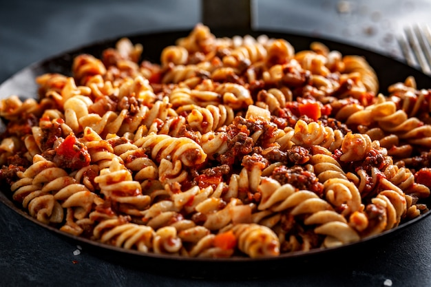 Classic italian pasta with minced meat and vegetables cooked and served on pan. closeup.