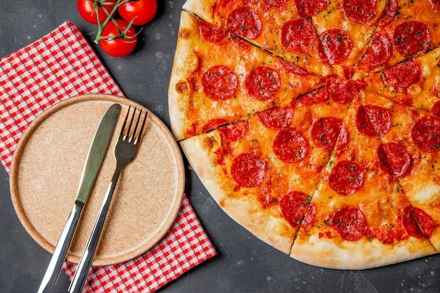 고전적인 이탈리아 페퍼로니 피자와 빈 접시, 평면도. 고품질 사진