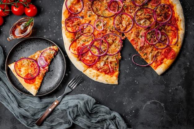 접시, 평면도에 양파와 함께 고전적인 이탈리아 페퍼로니 피자. 고품질 사진