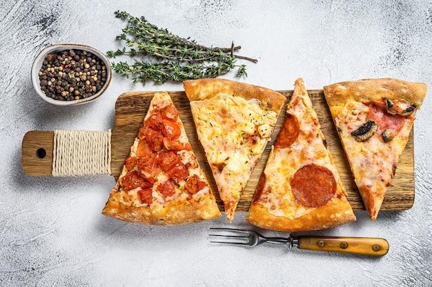 Классическая итальянская пицца на деревянной разделочной доске. белый фон. вид сверху.