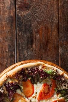 素朴な木のテーブルで提供される古典的なイタリアのピザ