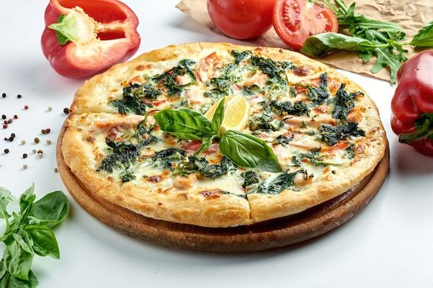 シーフード、サーモン、ほうれん草、パルメザンチーズ、ホワイトソースをプレートに乗せたクラシックなイタリアンピザ。白い表面