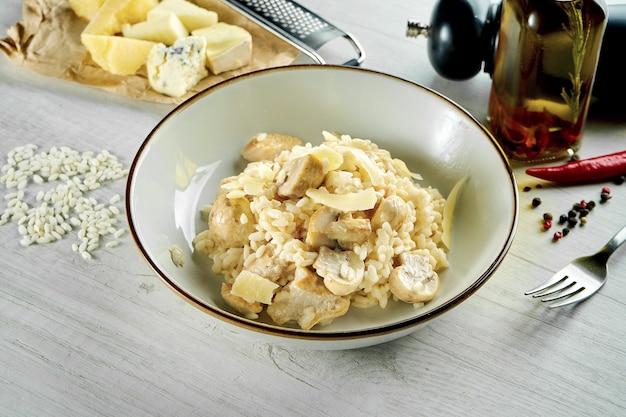 パルメザンチーズ、クリーミーソース、チキン、マッシュルームを添えたクラシックなイタリアンリゾットを、木製のテーブルの上の白いボウルでお召し上がりいただけます。レストランの食べ物