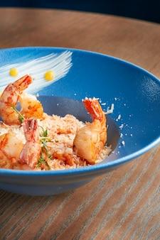 Классический итальянский ризотто с морепродуктами и пармезаном. рис с креветками в синюю тарелку на деревянной поверхности. эффект фильма во время поста. мягкий фокус