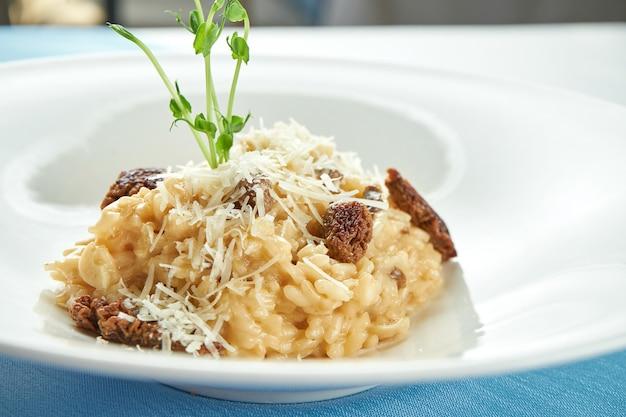Классическое итальянское ризотто с трюфелем и вялеными помидорами, сыром пармезан в белой тарелке на голубой скатерти.