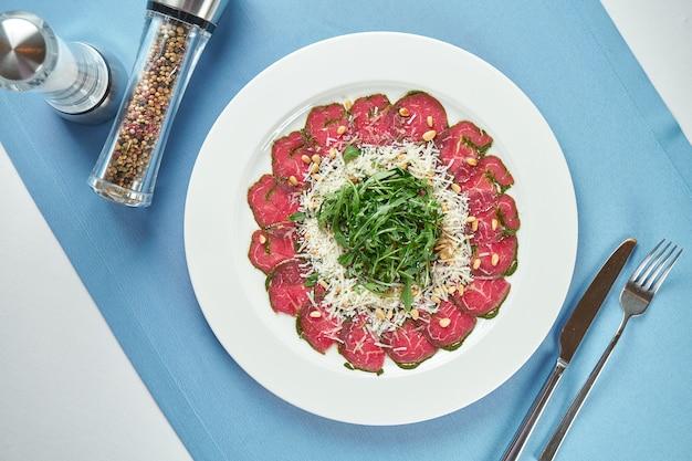 Классический итальянский салат - вителло тонато из говядины с рукколой, пармезаном и трюфельным соусом в белой тарелке на синей скатерти. крупным планом, выборочный фокус