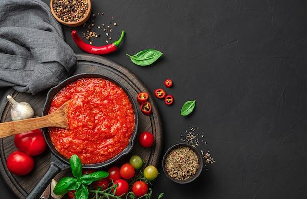 材料と黒の背景にバジルと古典的なイタリアのトマトソース。パスタ、ピザのソース。