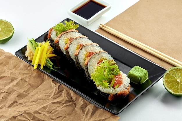 고전적인 일본 음식-구워서 살짝 소금에 절인 연어, 오이를 곁들인 후토 마키 스시 롤이 하얀 접시에 검은 접시에 담겨 있습니다. 클로즈업, 선택적 초점