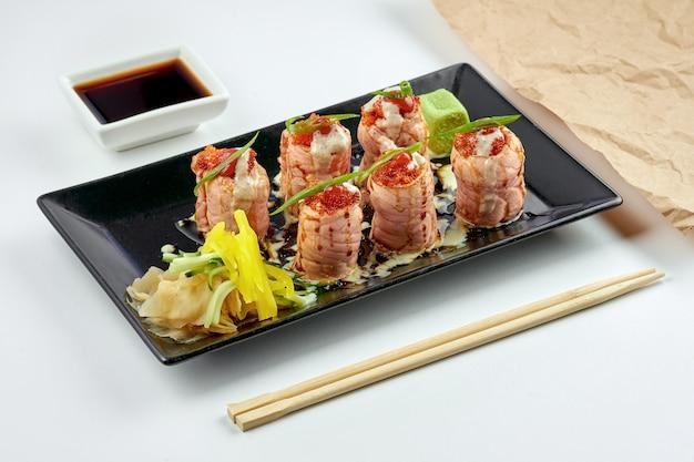 Классическая японская еда - суши-ролл «филадельфия» с икрой тобико и жареным лососем, белым соусом, подается в черной тарелке. на белой поверхности