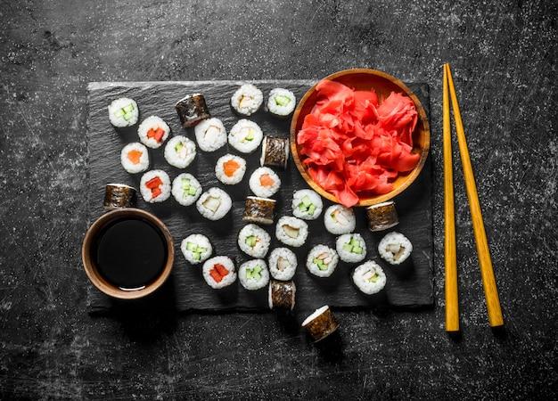 Классические японские роллы с имбирем и соевым соусом. на деревенском фоне