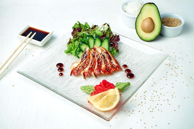 Классические японские сашими - сырой угорь с салатом на белой тарелке в композиции с ингредиентами