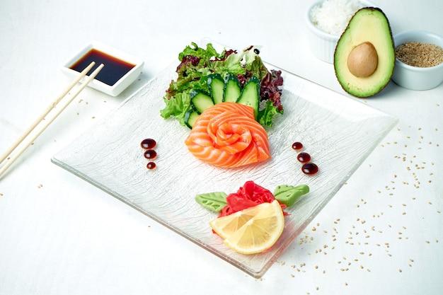 Классические японские сашими - сырой лосось с салатом на белой тарелке в композиции с ингредиентами