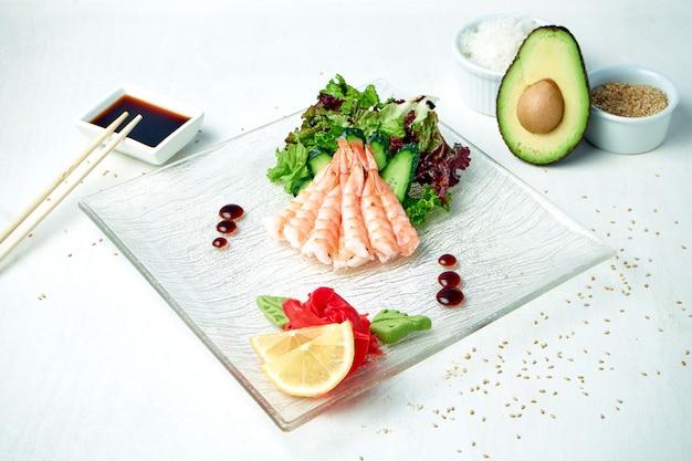 Классические японские сашими - креветки с салатом на белой тарелке в композиции с ингредиентами
