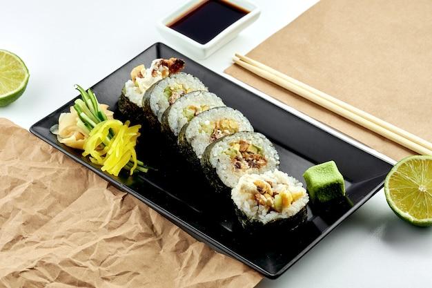 클래식 일본 스시 롤-오이, 크림 치즈, 구운 연어를 곁들인 후토 마키가 검은 접시에 제공됩니다. 흰색 표면