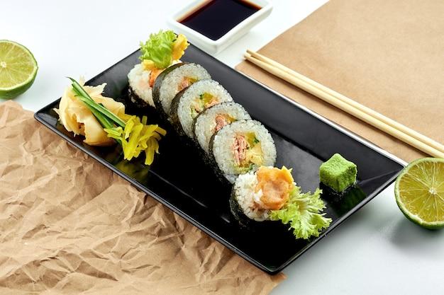클래식 일본 스시 롤-오이, 크림 치즈, 튀김 연어를 곁들인 후토 마키가 검은 접시에 제공됩니다. 흰색 표면