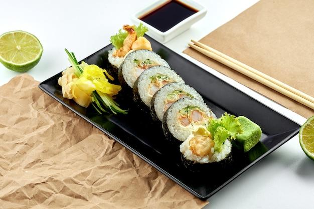 Классический японский суши-ролл - футомаки с огурцом, сливочным сыром и креветками темпура, подается в черной тарелке. белая поверхность