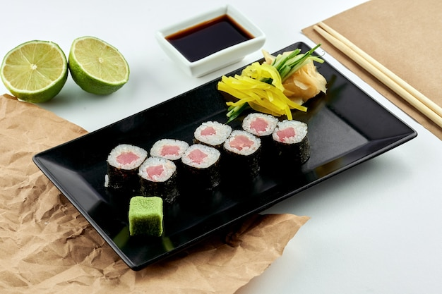 Classic japanese sushi roll - hosomaki with tuna, served in a black plate. white surface