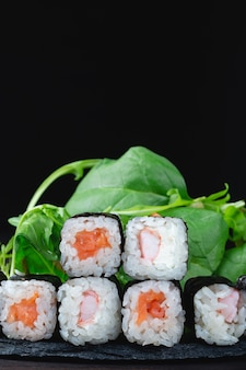 Классические японские суши-роллы крупным планом на темном фоне