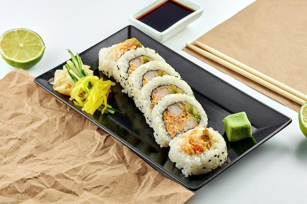 Классические японские суши-роллы с начинкой. урамаки с авокадо, яичницей и креветками темпура, подается на черной тарелке. белая поверхность