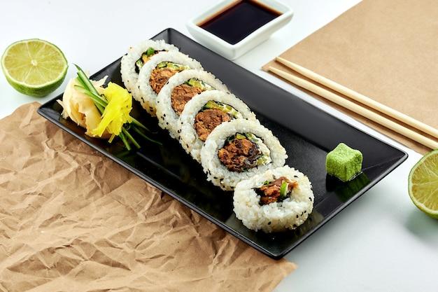 Классические японские суши-роллы с начинкой. урамаки с огурцом, луком и запеченным лососем, подается в черной тарелке