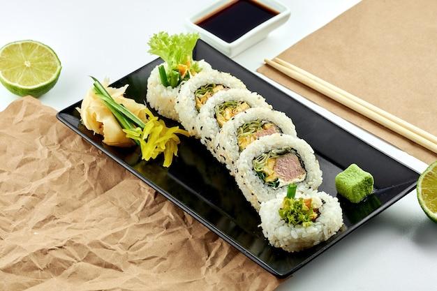 Классические японские суши-роллы с начинкой. урамаки с огурцом, луком и тунцом в темпуре, подается на черной тарелке. белая поверхность